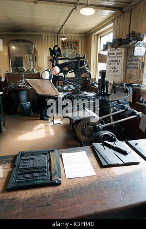 older male printer working on vintage flatbed letterpress printing machine surrounded by vintage printing machinery - Stock Photo