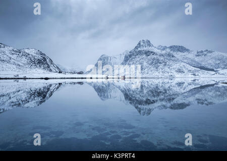 Perfect reflection of mountains and red house, Lofoten Islands, Norway - Stock Photo