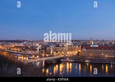Dusk lights up the historical bridges and buildings reflected on Vltava (Moldava) river Prague Czech Republic Europe - Stock Photo
