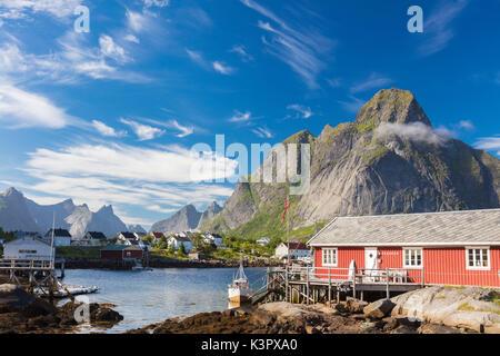 Typical house of fishermen called Rorbu framed by rocky peaks and blue sea Reine Moskenes Lofoten Islands Norway - Stock Photo