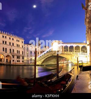 The famous Rialto bridge in Venice under a romantic moonlight and some gondolas in the foreground - Venice, Veneto, - Stock Photo