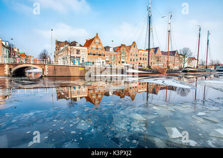 Buildings in Harleem reflecting in the half-frozen Spaarne River, about 20 km from Amsterdam, Holland, Netherlands - Stock Photo