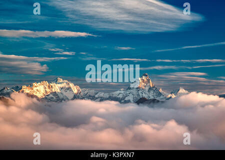 The morning fog of an autumn morning trying to conceal the majesty of the Matterhorn, Dent d'Herens and Weisshorn - Stock Photo
