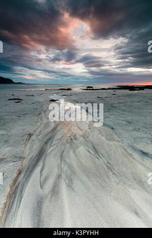 Midnight sun and clouds frame the sandy beach of Skagsanden Flakstad Nordland county Lofoten Islands Norway Europe - Stock Photo