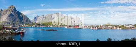 Panorama of the blue sea surrounding the fishing village and rocky peaks Reine Moskenes Lofoten Islands Norway Europe - Stock Photo