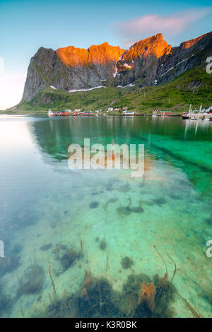 Midnight sun on fishing village surrounded by clear sea and peaks Reine Nordland county Lofoten Islands Northern - Stock Photo