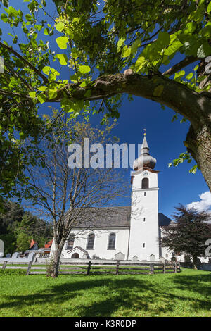 Typical church of alpine village surrounded by peaks and woods Garmisch Partenkirchen Oberbayern region Bavaria - Stock Photo
