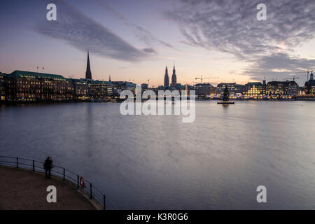 Photographer admires the Inner Alster Lake with the Christmas Tree suspended in its water at dusk Hamburg Germany - Stock Photo
