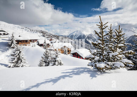 The winter sun shines on the snowy mountain huts and woods Bettmeralp district of Raron canton of Valais Switzerland - Stock Photo