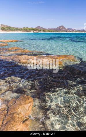 Rocks frame the turquoise water of sea around the sandy beach of Sant Elmo Castiadas Costa Rei Cagliari Sardinia - Stock Photo