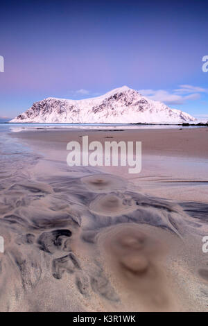 Pink sky and snowy peaks frame the surreal Skagsanden beach at sunset Flakstad Nordland county Lofoten Islands Norway - Stock Photo