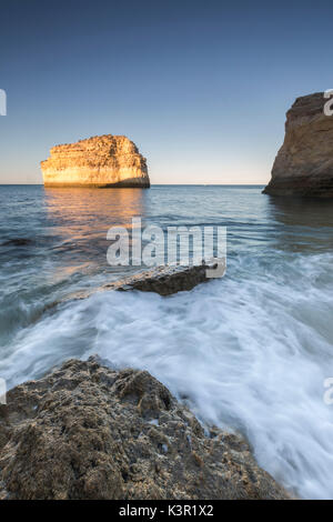 Ocean waves crashing on rocks at sunrise Praia De Albandeira  Carvoeiro Caramujeira Lagoa Municipality Algarve Portugal - Stock Photo
