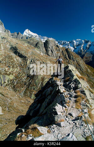Hiker overlooking towards the Mount Disgrazia by a walking section of the trail Rome. Valmasino. Valtellina. Lombardy - Stock Photo