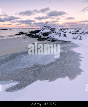 Colorful arctic sunset on the lighthouse surrounded by ice and snow Eggum Vestvagoy Island Lofoten Islands Norway - Stock Photo