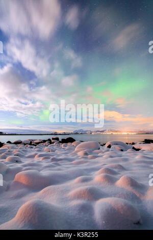 The pink light and the aurora borealis illuminate the snowy landscape on a starry night Strønstad Lofoten Islands - Stock Photo