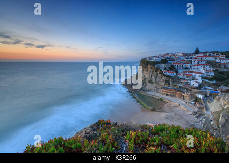 The soft colors of twilight frame the ocean and the village of Azenhas do Mar Sintra Portugal Europe - Stock Photo