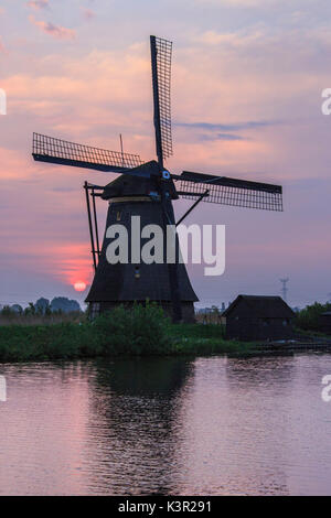 Pink sky at sunrise on the windmill reflected in the canal Kinderdijk Rotterdam South Holland Netherlands Europe - Stock Photo