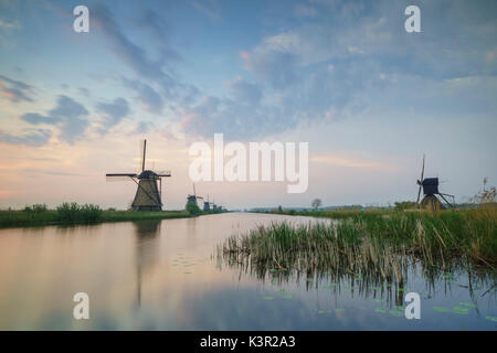 Blue sky and pink clouds on the windmills reflected in the canal at dawn Kinderdijk Rotterdam South Holland Netherlands - Stock Photo