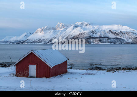 A typical house of fishermen called rorbu in the snowy landscape of Lyngen Alps Tromsø Lapland Norway Europe - Stock Photo