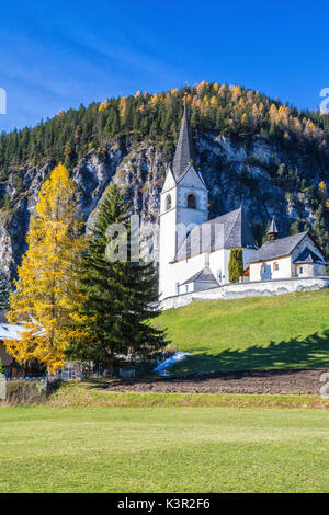 The church of Schmitten surrounded by colorful woods Albula District Canton of Graubünden Switzerland Europe - Stock Photo