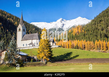 The church of Schmitten surrounded by colorful woods and snowy peaks Albula District Canton of Graubünden Switzerland - Stock Photo