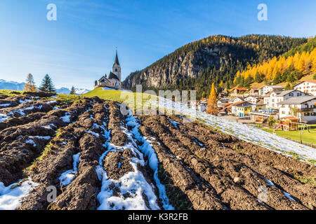 The church of Schmitten surrounded by colorful woods and snow Albula District Canton of Graubünden Switzerland Europe - Stock Photo