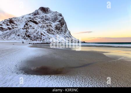 Dawn illuminates the partially snow covered beach of Uttakleiv. Lofoten Islands Norway Europe - Stock Photo