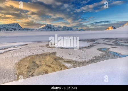 The golden sunrise reflected in a pool of the clear sea where the snow is almost melted. Haukland Lofoten Islands Norway Europe