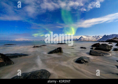 Northern Lights illuminate the landscape around Gymsøyand and the snowy peaks. Lofoten Islands Northern Norway Europe - Stock Photo