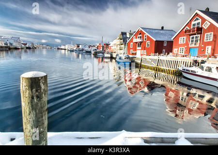 View from the pier on the channel Henningsvaer overlooked by the fishermens houses. Lofoten Islands. Norway. Europe - Stock Photo