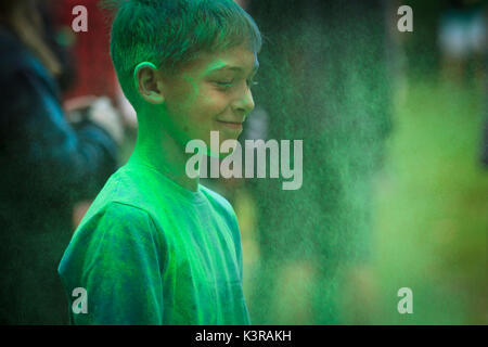 Portrait of smiling boy taken during holi festival of colours. Cieszyn, Poland. - Stock Photo