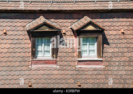 Bamberg, Germany - May 22, 2016: Traditional windows on the tiled roof of old half-timbered colorful house close - Stock Photo