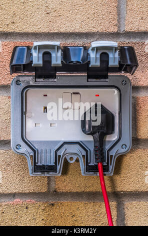 Plug and lead in an outside power supply on a residential house wall, mainly for garden use. Three pin, British, - Stock Photo