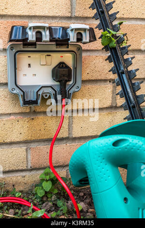 Hedge trimmer plugged into an outside power supply on a residential house wall. Three pin, British, twin electrical - Stock Photo