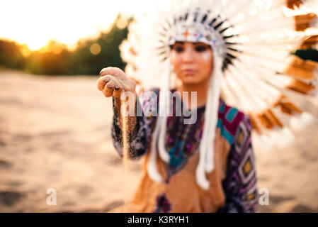 Beautiful woman in a suit of the American Indian play with sand on sunset. Young girl in headdress made of feathers - Stock Photo