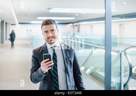 Businessman is looking at his mobile phone while is going to work - Stock Photo