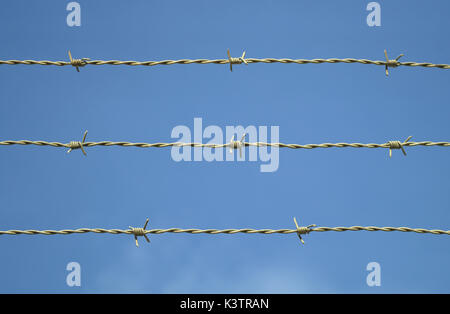 metal fence barbed wire on blue sky closed boundary - Stock Photo