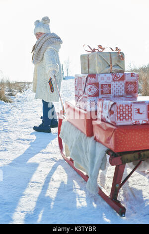 Girl pulling sled full of christmas gifts in winter - Stock Photo