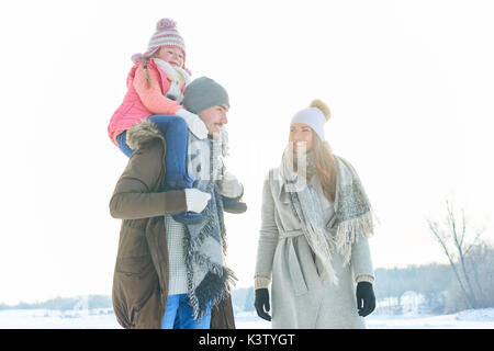 Family on their winter vacation walking in the snow in the nature - Stock Photo