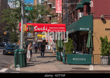 New York, NY USA August 3, 2016 --Photo of pedestrians and colorful restaurants on the corner of West 22nd Street - Stock Photo