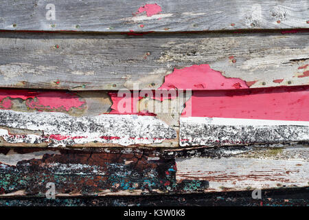Fantastic cracked and faded paint on the side of on old fishing boat dry docked on St Leonards beach, Hastings, - Stock Photo