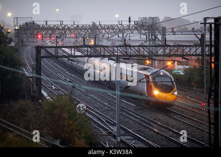 From London Virgin Alstom Class 390 Pendolino at Ardwick leading to Manchester Piccadilly station on the  West Coast - Stock Photo