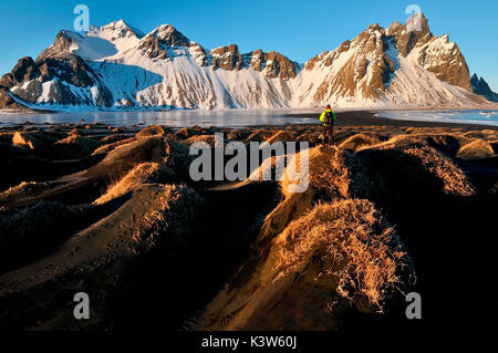 A man admires the Stokksnes mountains in the warm sunset light. Iceland - Stock Photo
