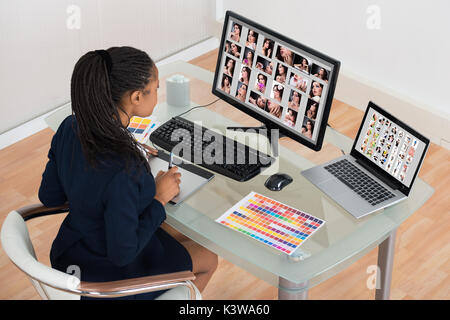 Young African Designer Retouching Photos On Computer - Stock Photo