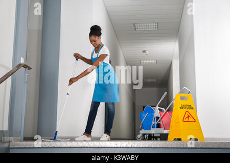 African Woman Mopping Corridor Besides Caution Sign - Stock Photo