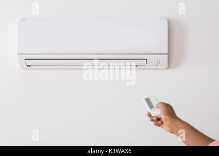 Close-up Of A Person's Hand Holding Remote To Operate Air Conditioner - Stock Photo