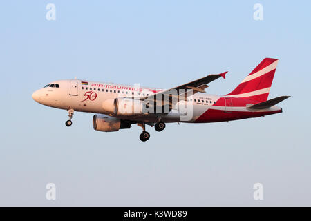 Air Mauritius Airbus A319 jet airplane flying on approach at sunset - Stock Photo