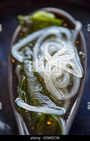 Closeup of miso soup with seaweed, noodles, seaweed and tofu on the spoon - Stock Photo