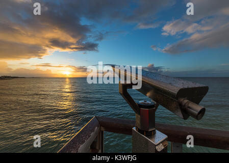 Telescope with water drops at lookout on the pier of Heiligenhafen in front off colorful sunset over the Baltic - Stock Photo