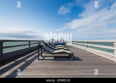 People sunbathing on deck chairs on the pier of Heiligenhafen on the Baltic Sea, Schleswig-Holstein, Germany - Stock Photo